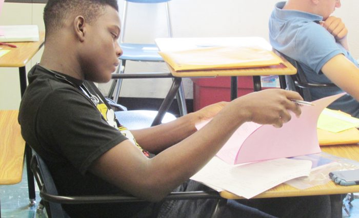 high school boy reading at his desk