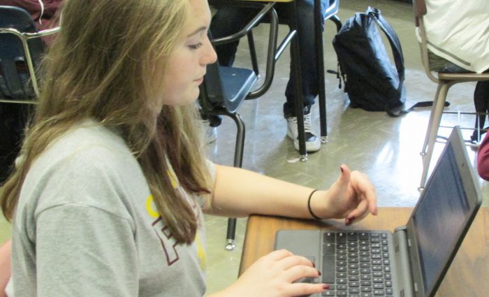 high school girl works on her Chromebook