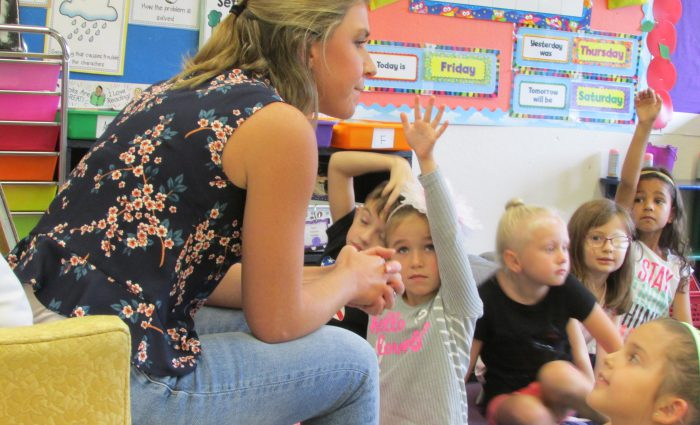 teacher leans over from chair to talk to her young students sitting on the classroom floor