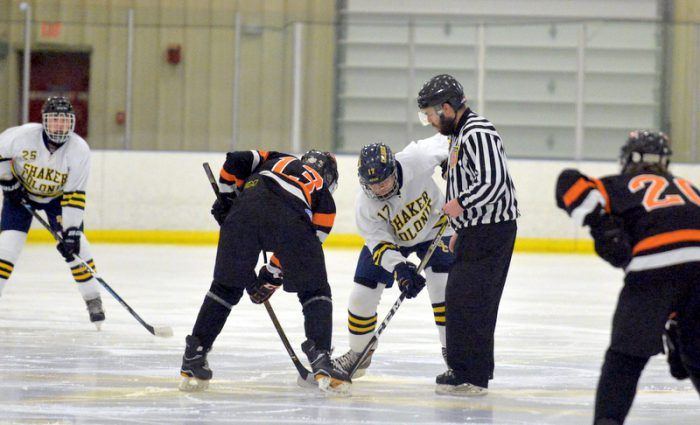 hockey players during a facebook as the puck drops by referee