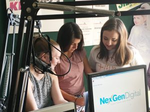 3 high school girls speak into microphone at radio station