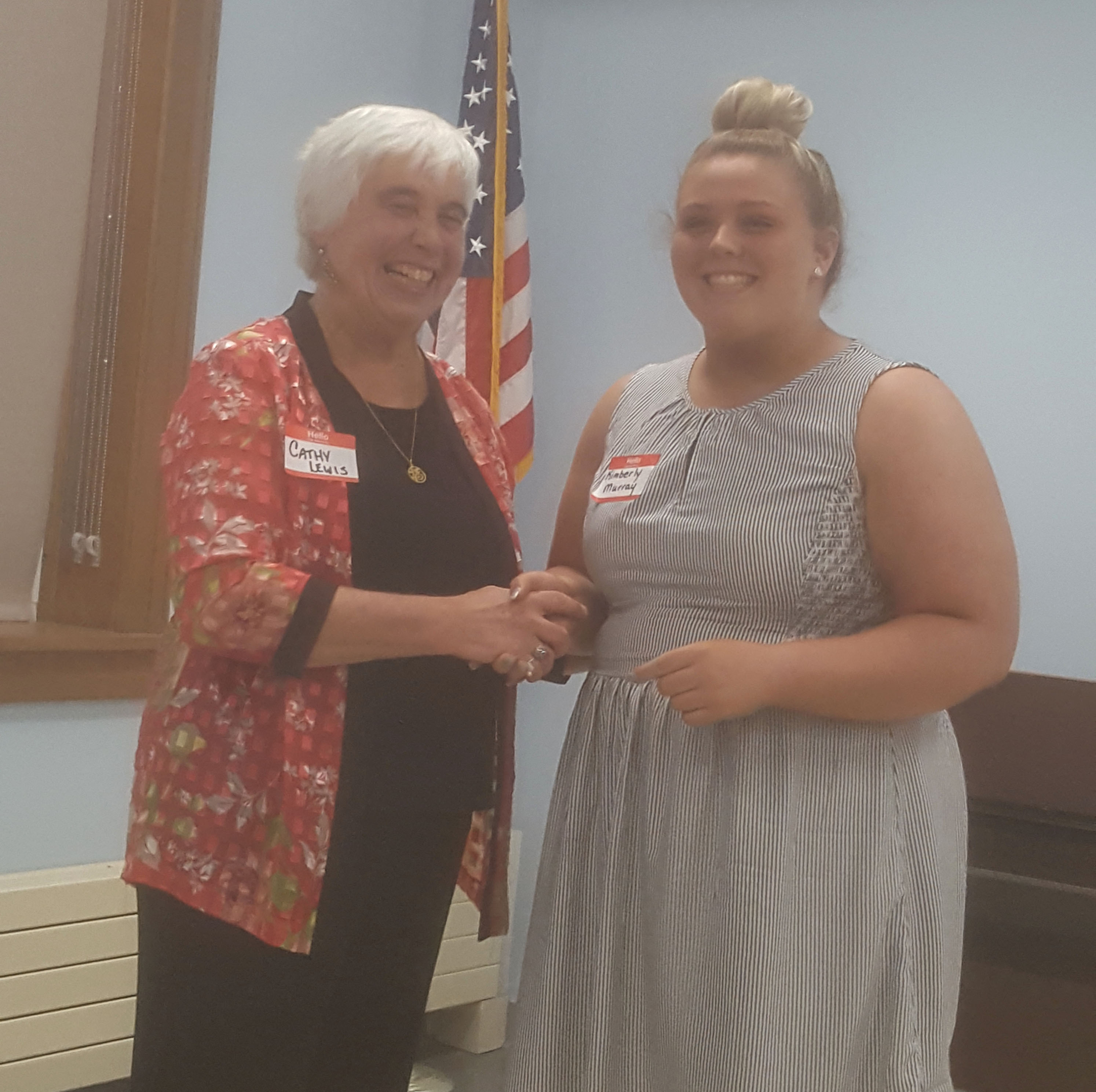 woman presents award to a high school student