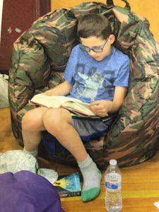 boy reading a book in a bean bag chair