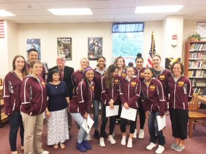 the girls basketball team poses with the school board