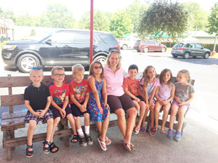 teacher sits on a bench with a group of kindergarten students