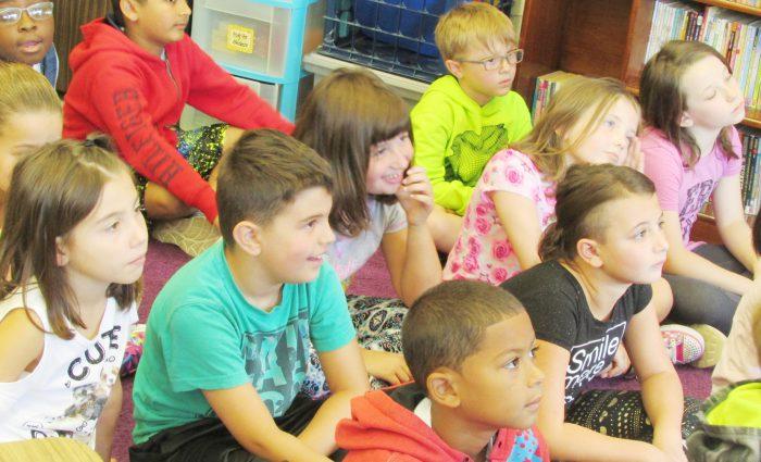 students sitting cross-legged on floor