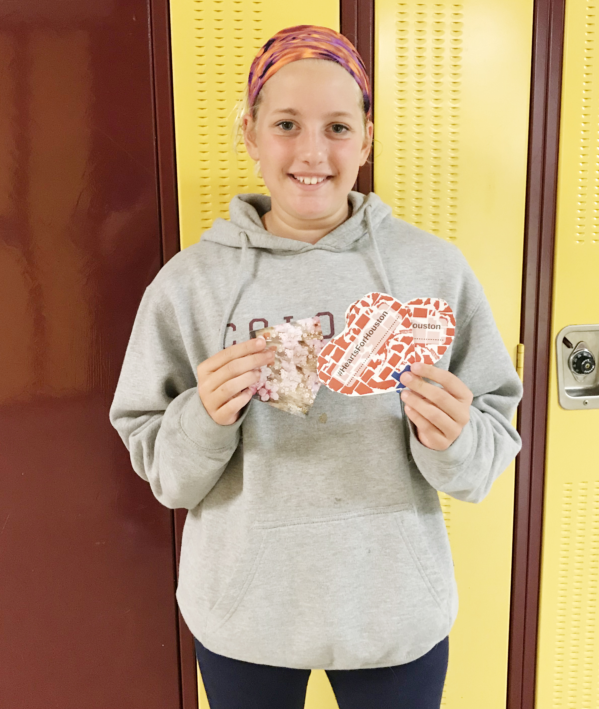 a middle school girl holds up a paper heart in front of her locker
