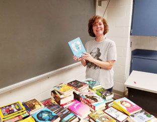 teacher sorts stacks of books on a table