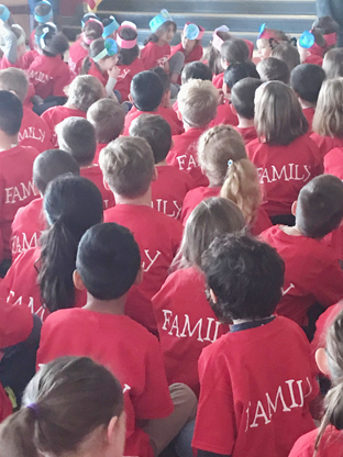 large group of children sitting on the floor showing the backs of their red T shirts