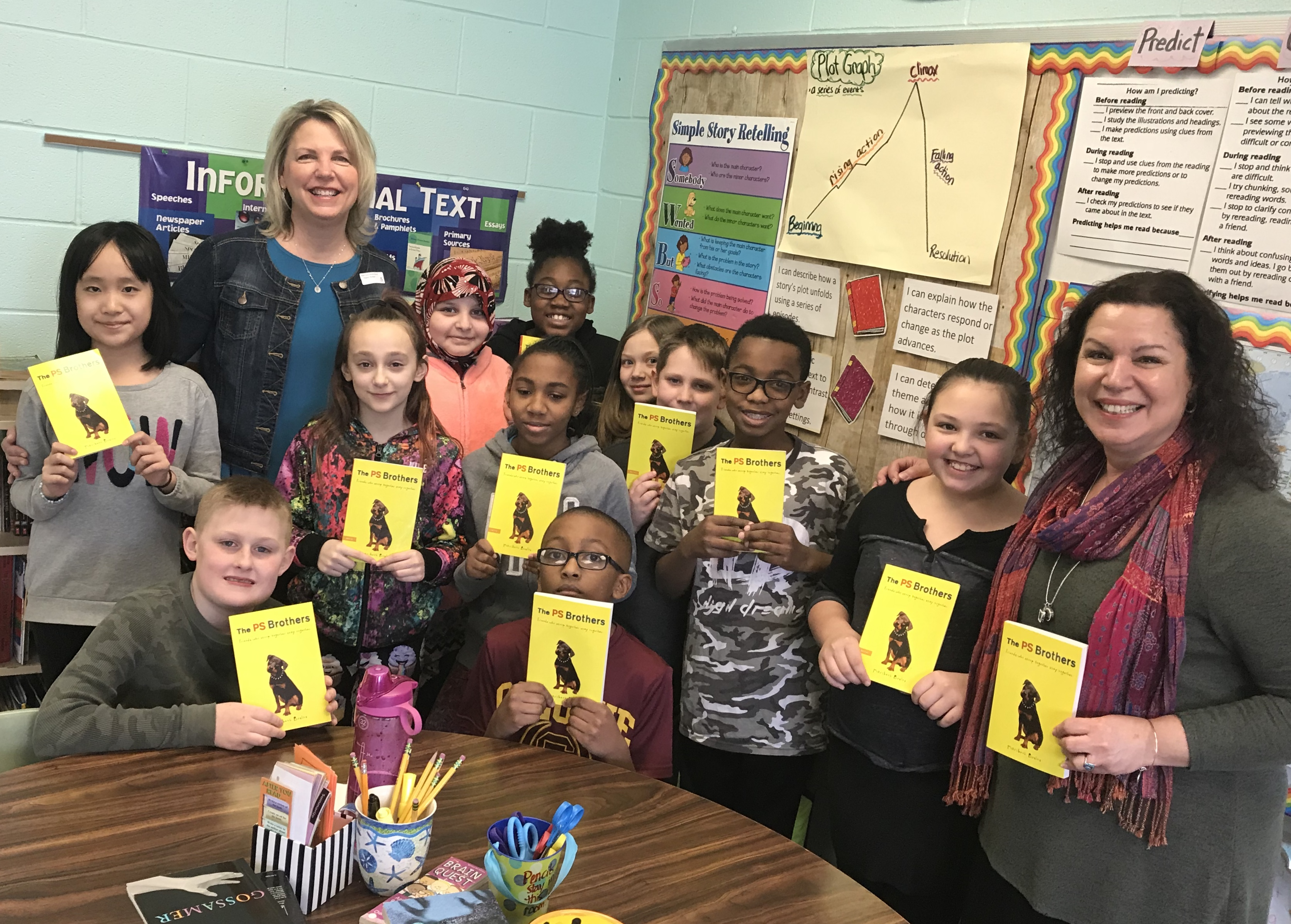 5th graders stand with author showing off her book