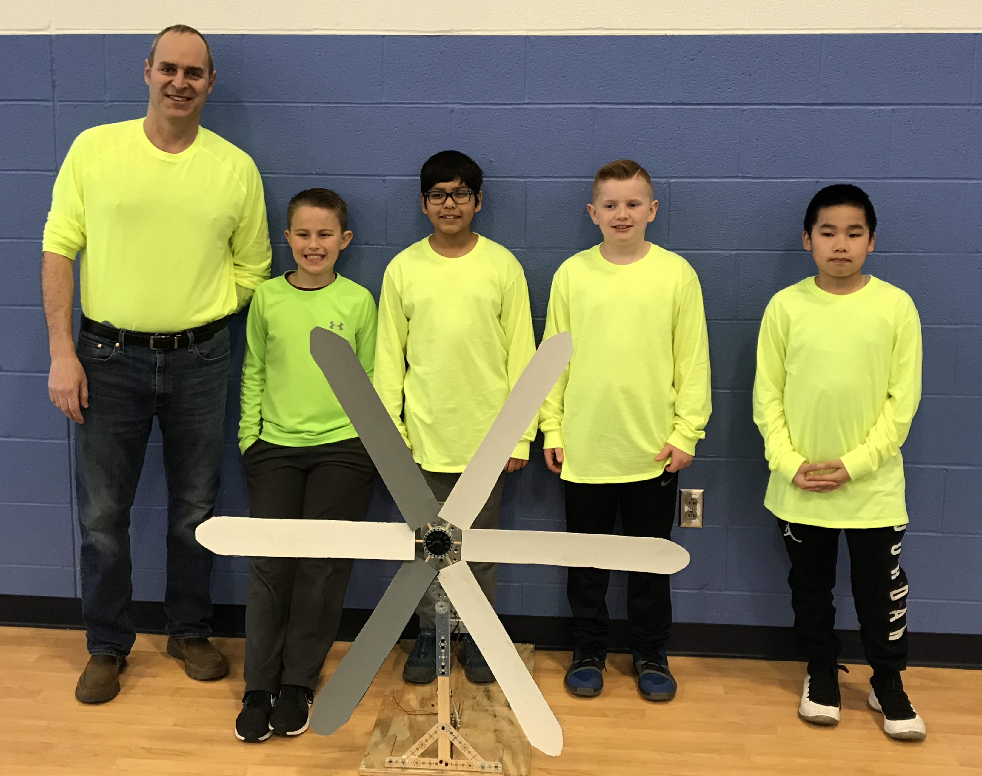 four students and their teacher stand with their STEM design project