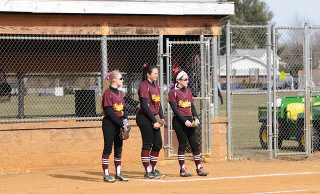 3 softball players stand for national anthem