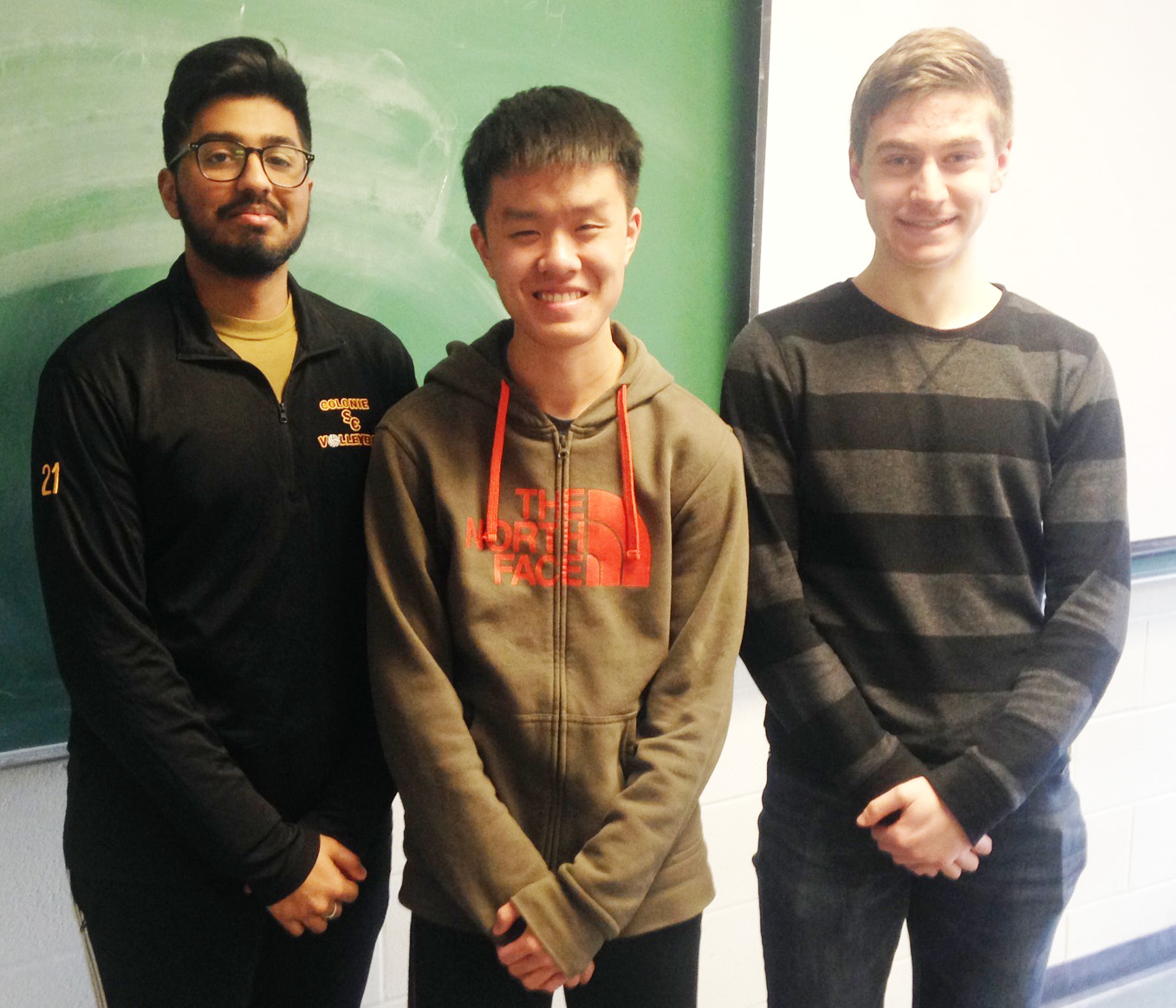 three high school students stand together