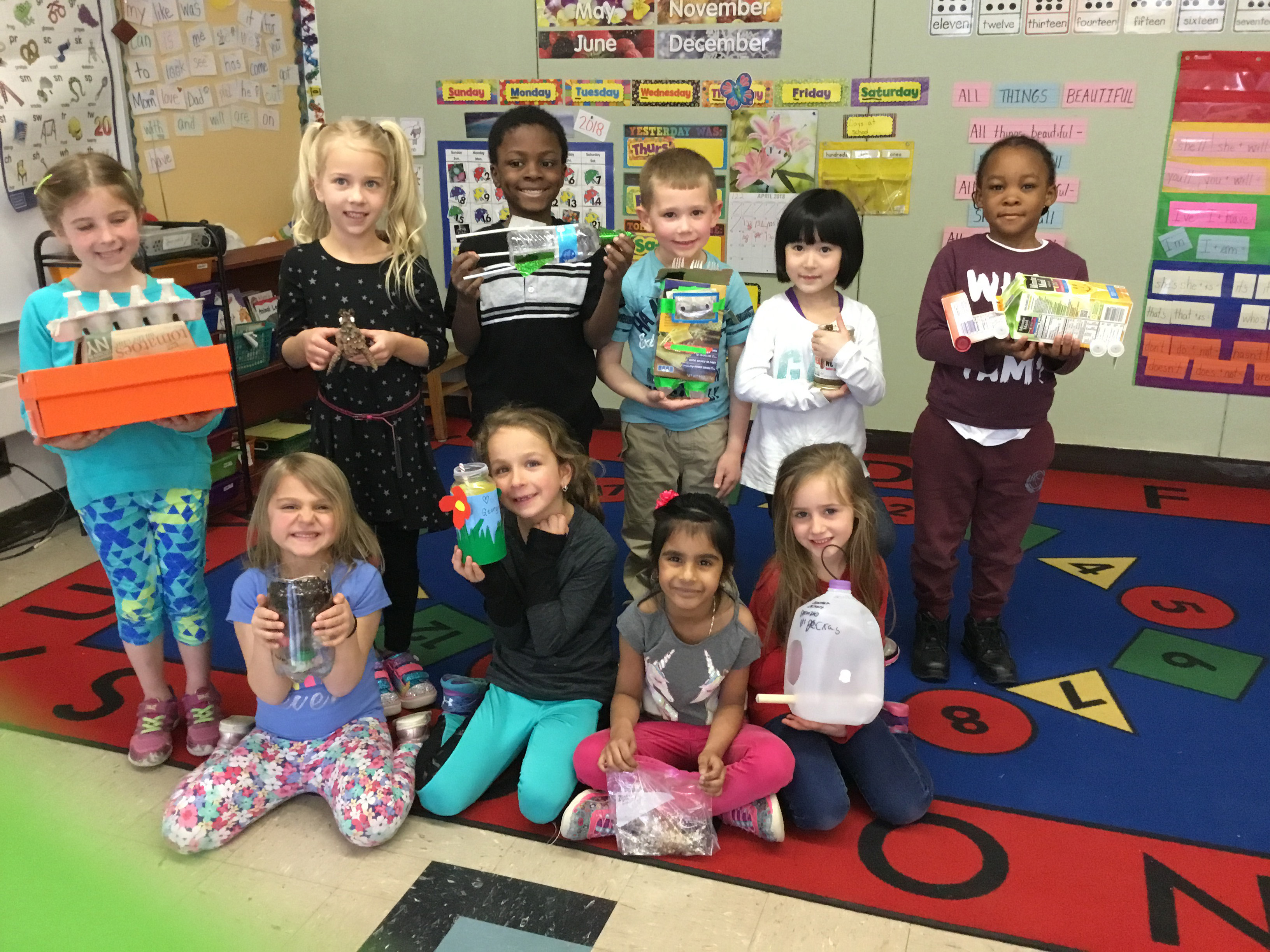 children show their recycled items