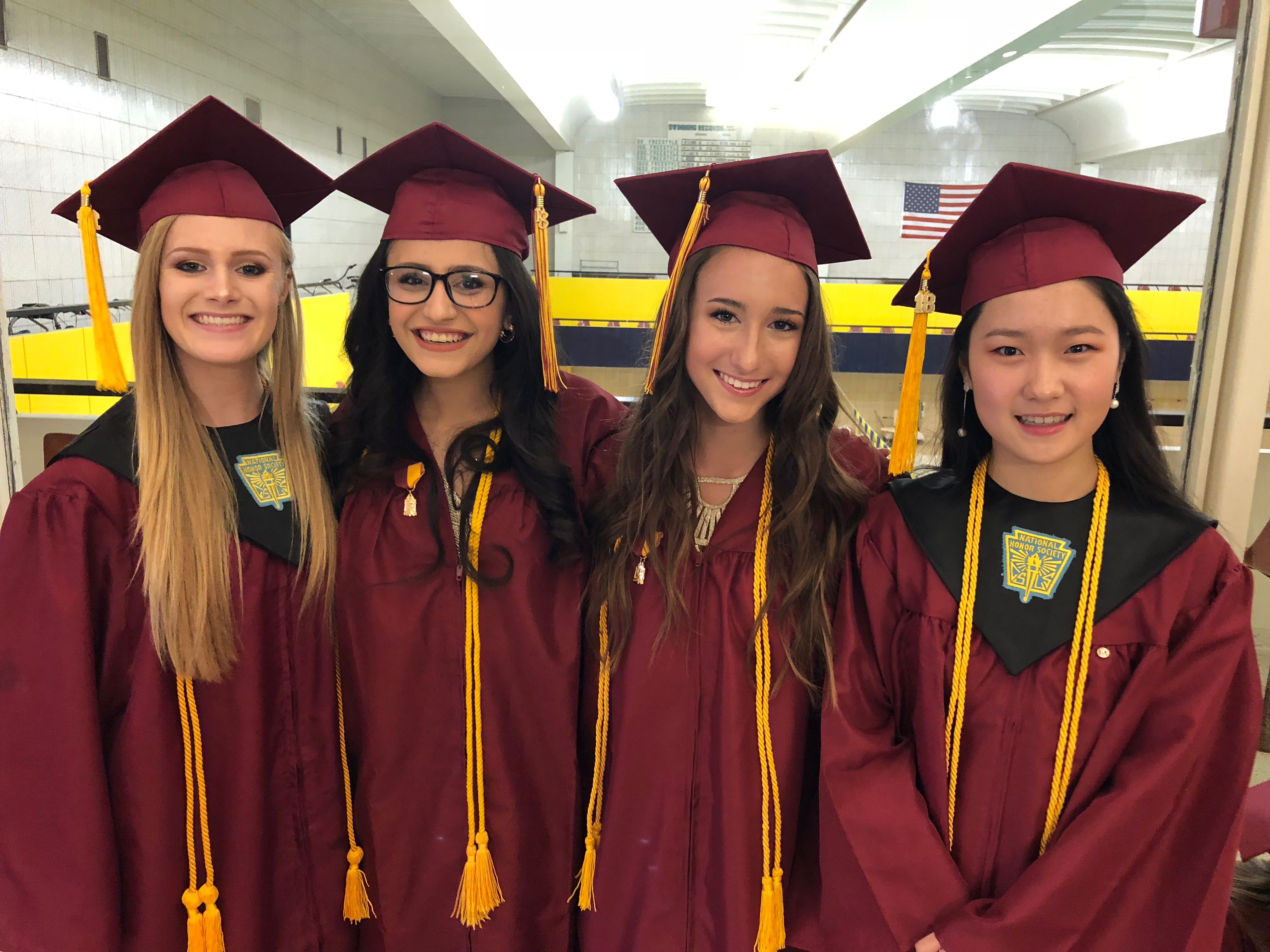 4 female graduates pose in their caps and gowns