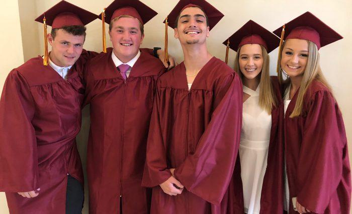 5 smiling grads pose