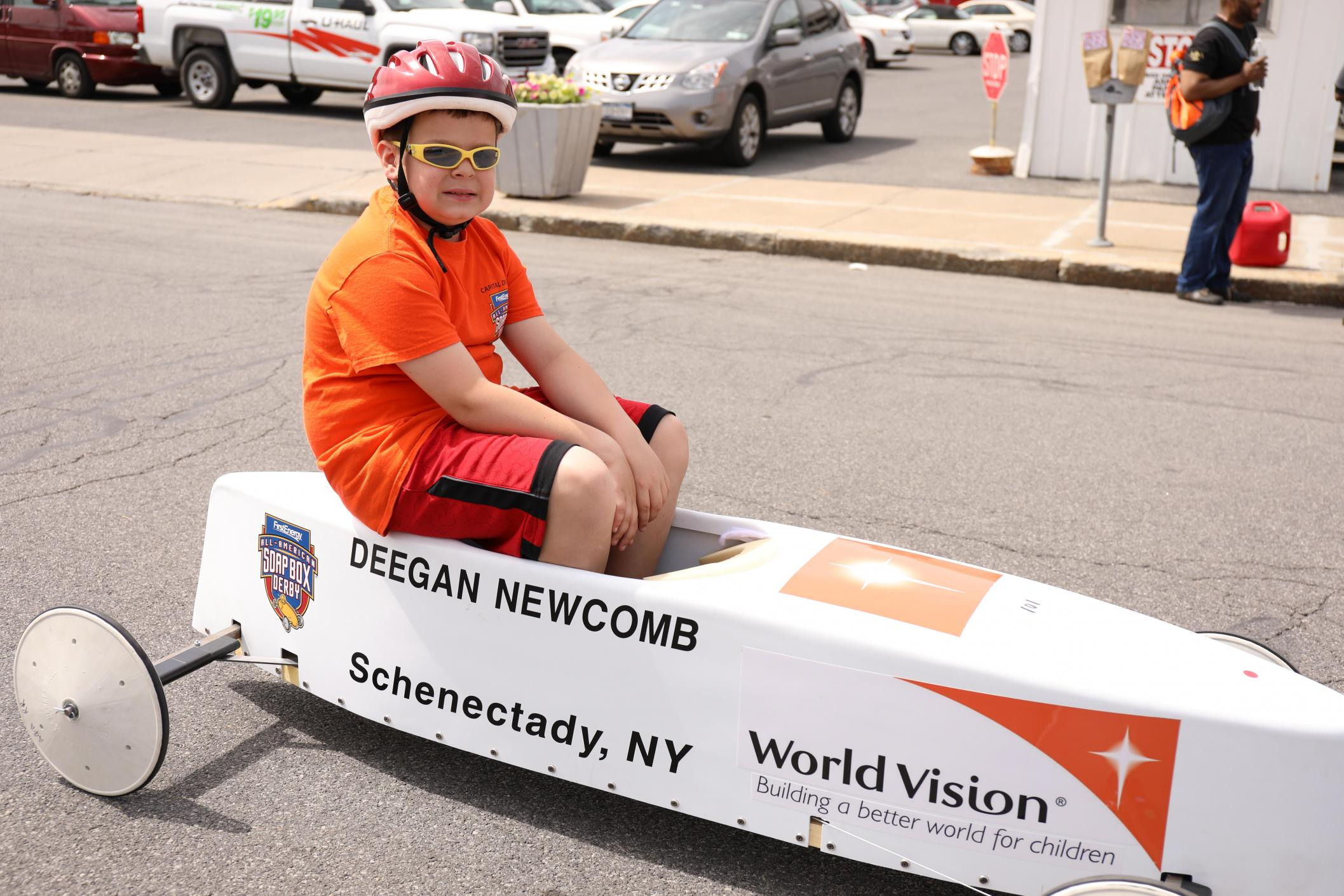 4th grader sits in his soap box derby car wearing a helmet and glasses