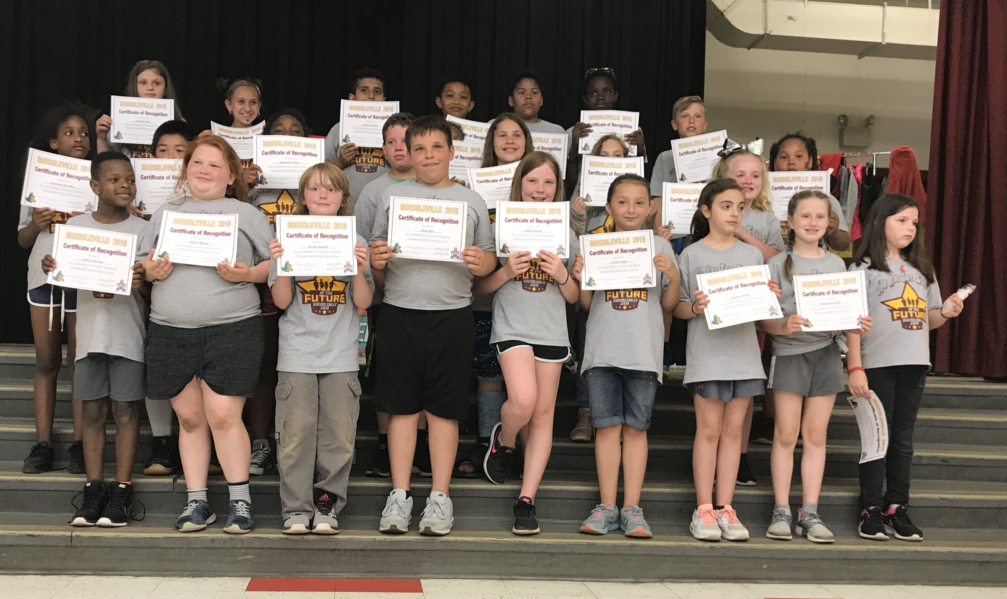 students stand with their award certificates