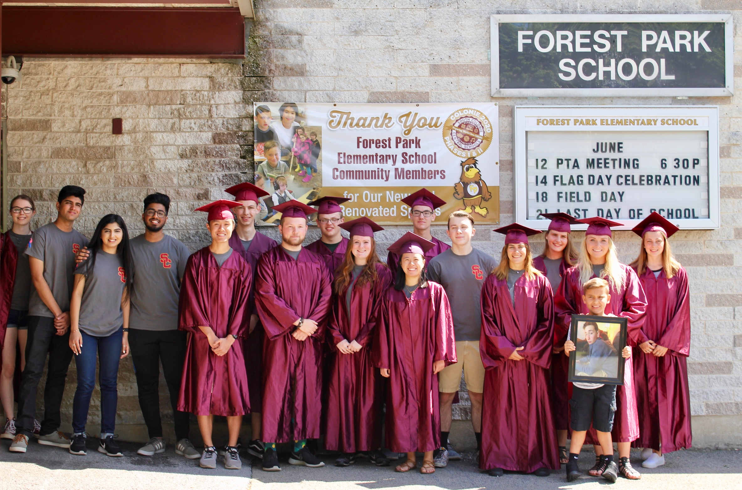 class of 2018 graduates pose as a group in their caps and gowns outside forest park school