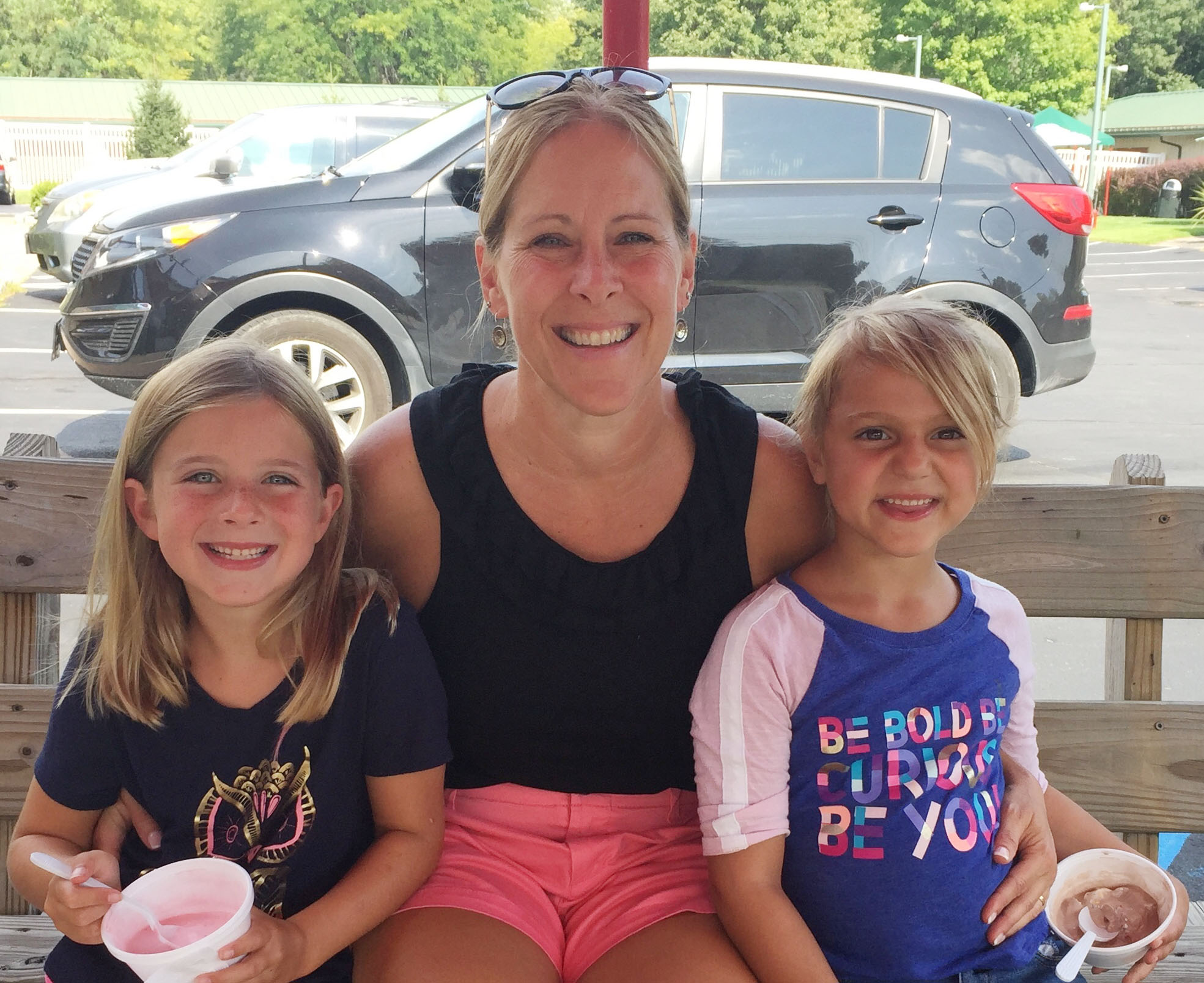 teacher sits with two kindergartners eating ice cream on a bench