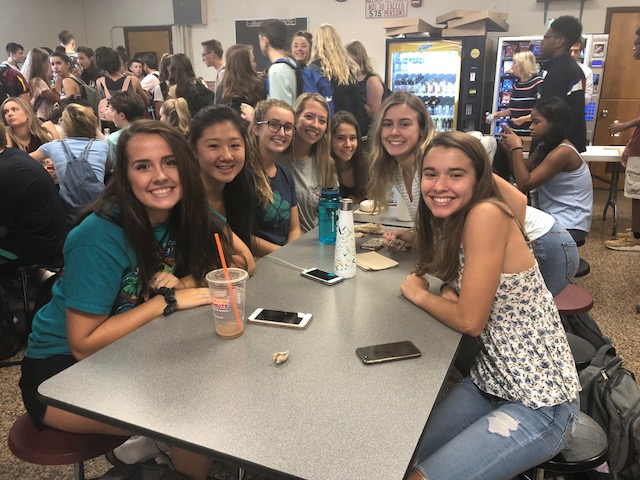 group of high school girls sitting around a cafeteria table smiling for the camera