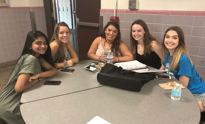 4 girls sitting at a cafeteria table