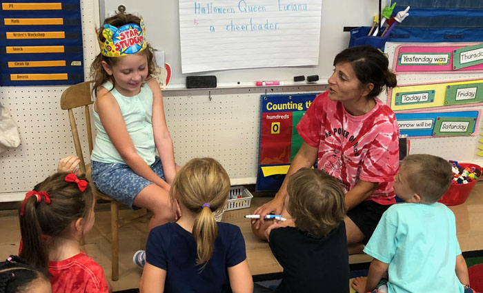 girl wearing crown sit in front of classmates with her teacher