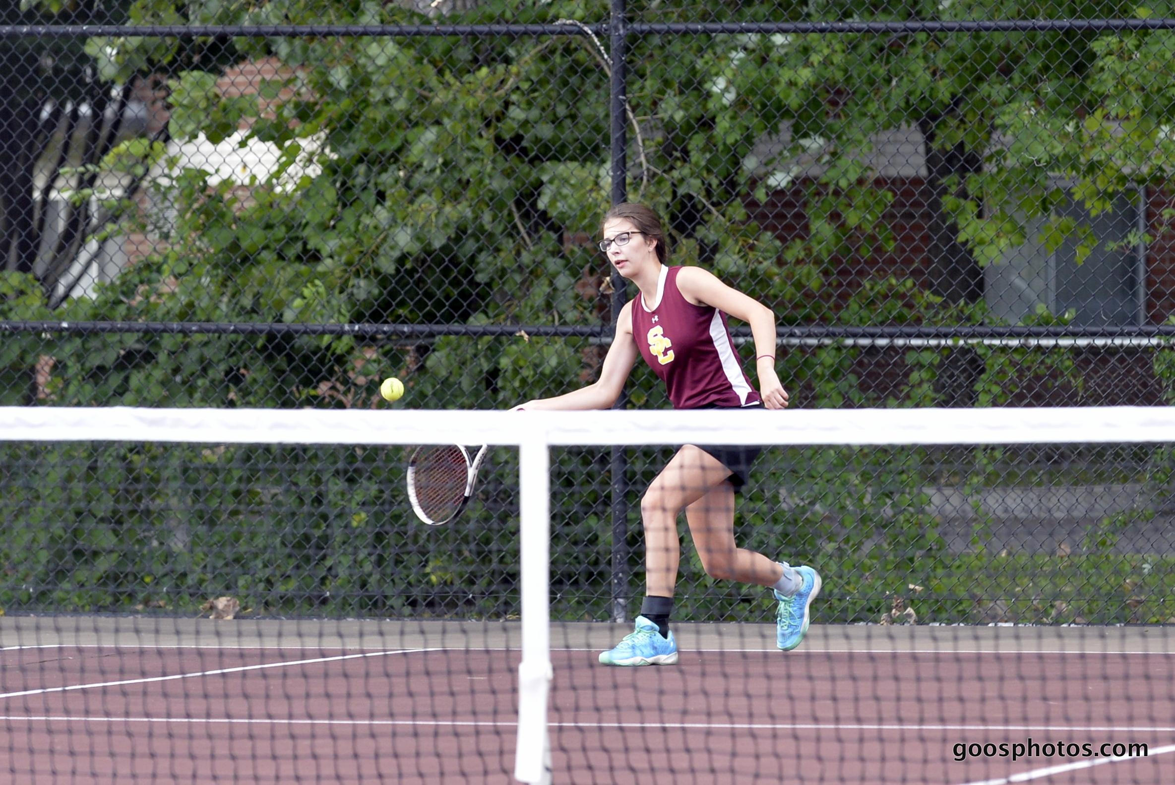 girl tennis player returns a shot