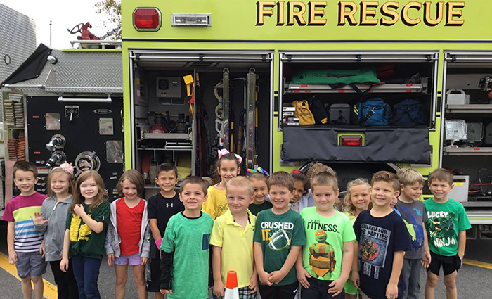 large group of kindergartners stand in front of fire engine