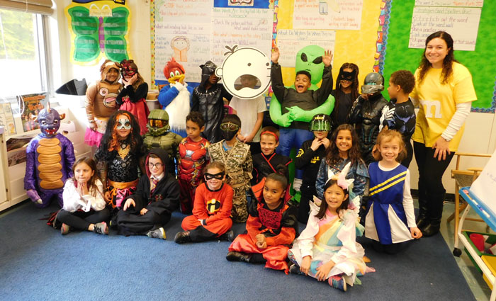 children sit in a group wearing their Halloween costumes