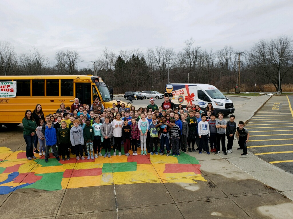 children stand in front of a school bus showing the toys they donated