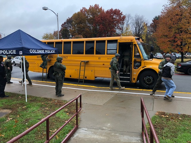 police conduct a safety drill outside a yellow school bus