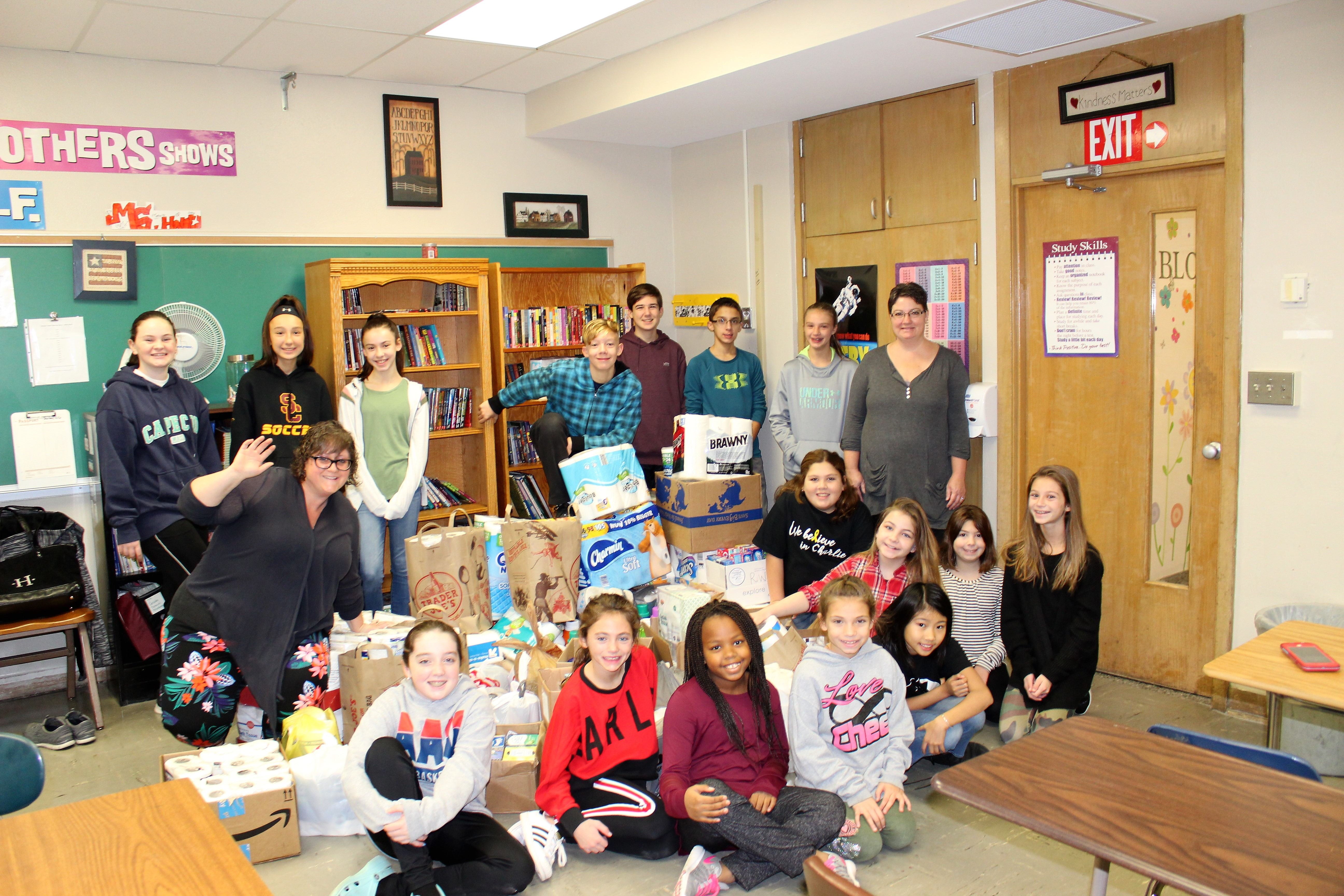 group of middle school students with supplies they collected