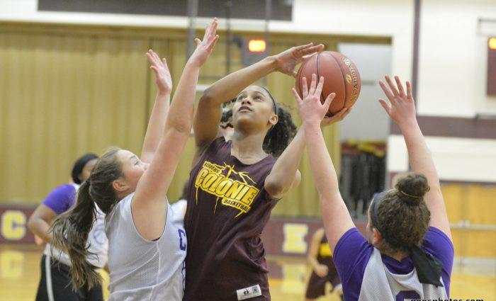 girl takes a basketball shot amongst defenders