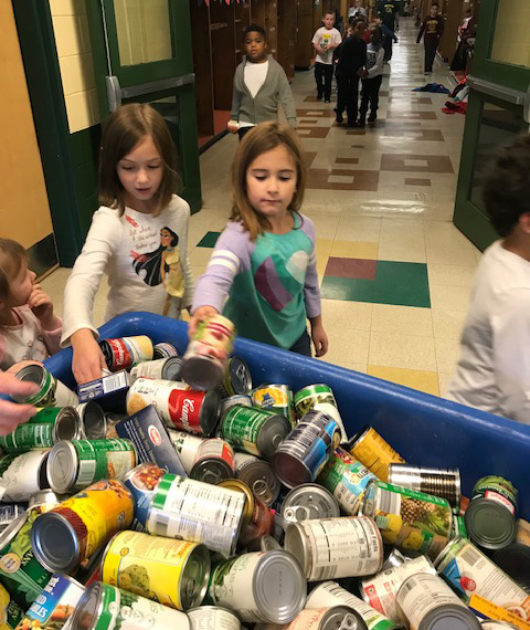 kids load canned good into a large bin