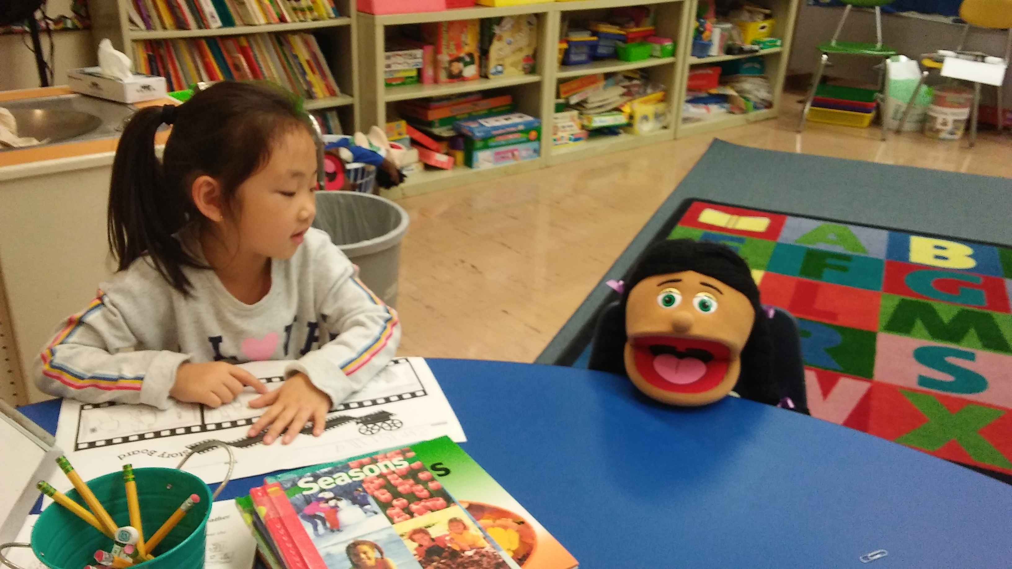 asian girl at a table with a puppet