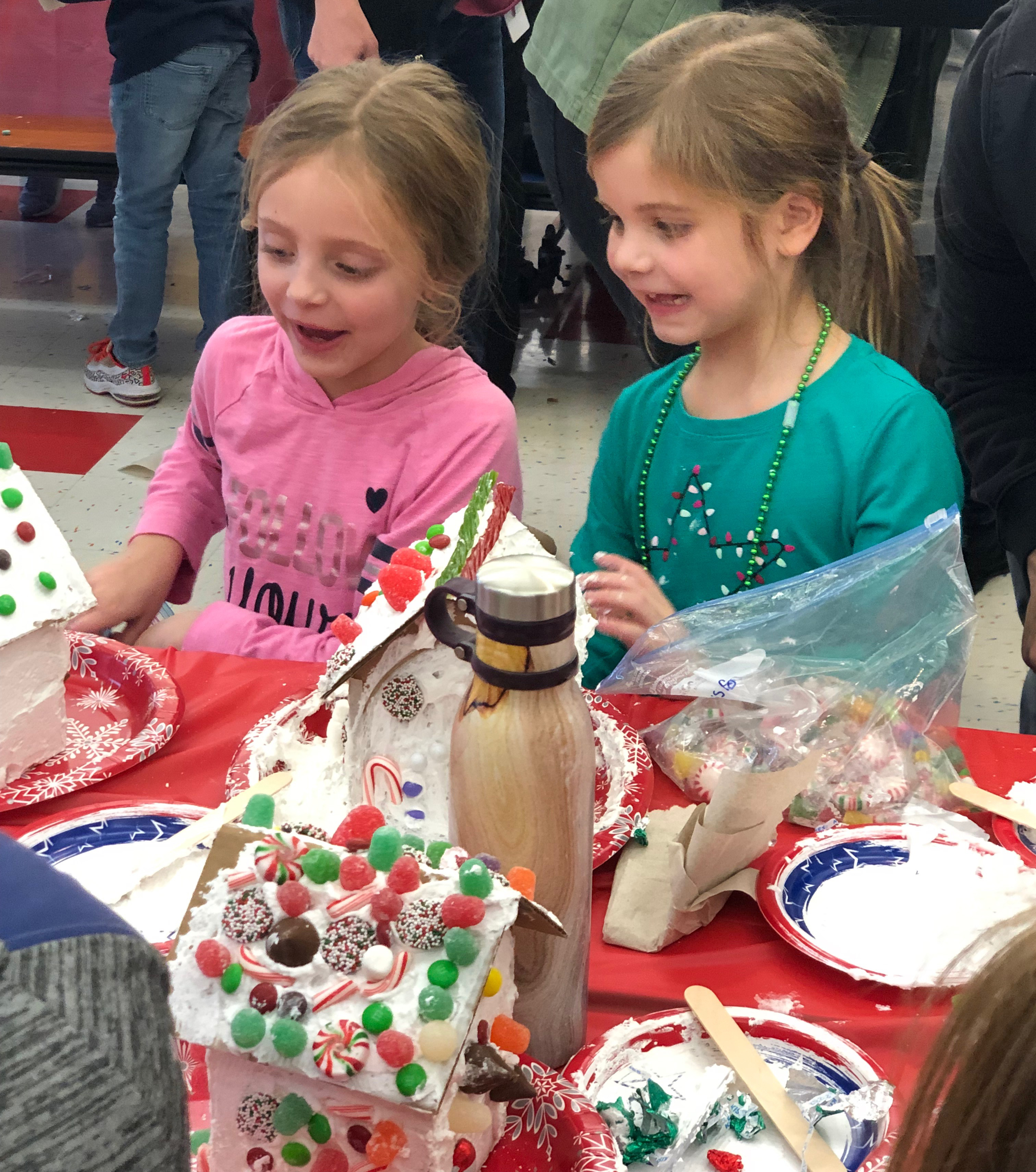 two girls put together a candy house together