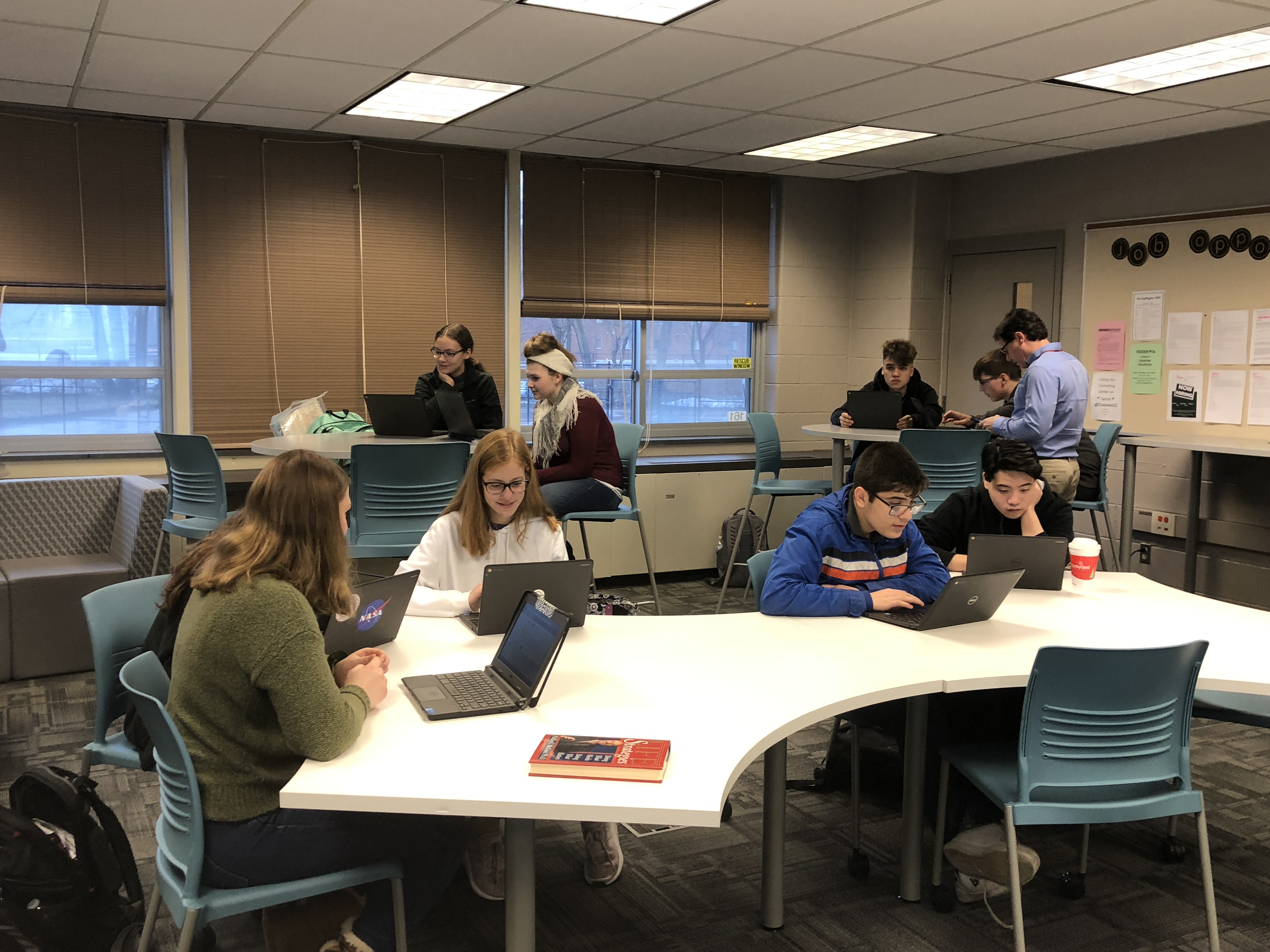 high school students work on laptops in the counseling center