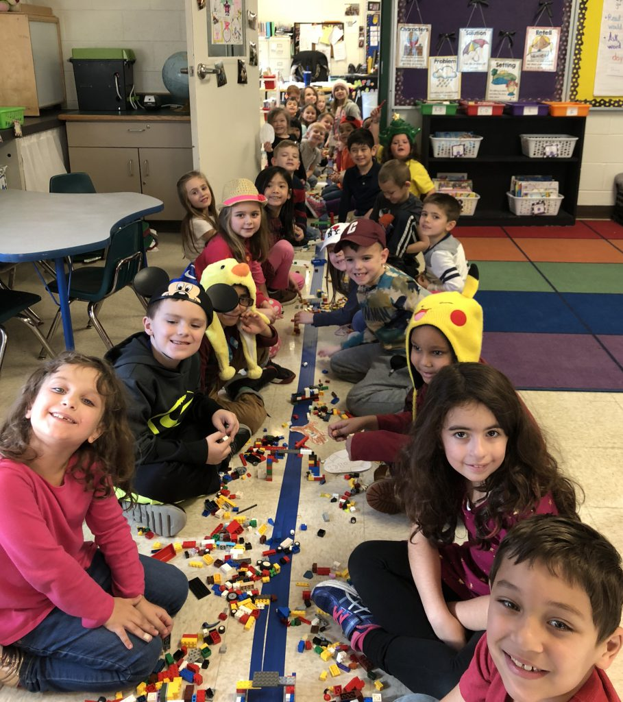 elementary students work together on a project on the floor