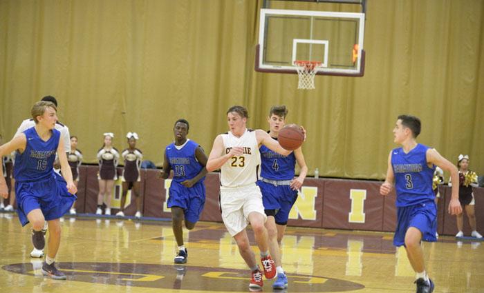 boy dribbles ball down basketball court among defenders