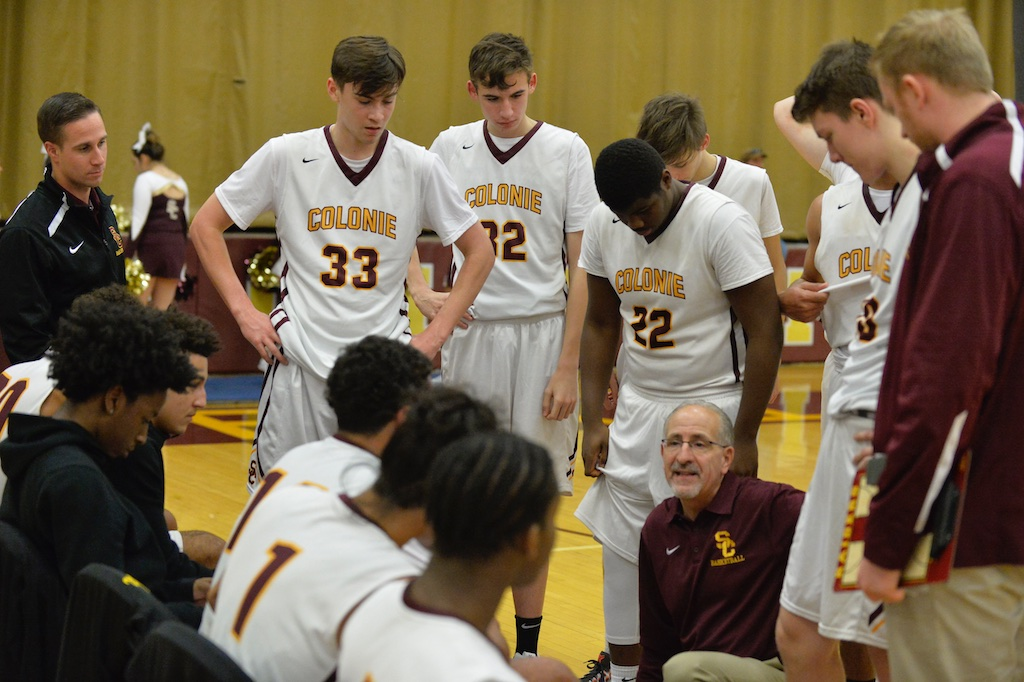 boys basketball players in a huddle with the coach