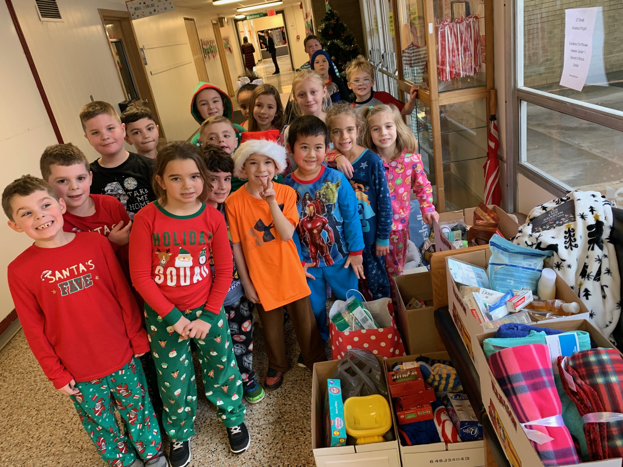 second graders stand in front of stacks of donations