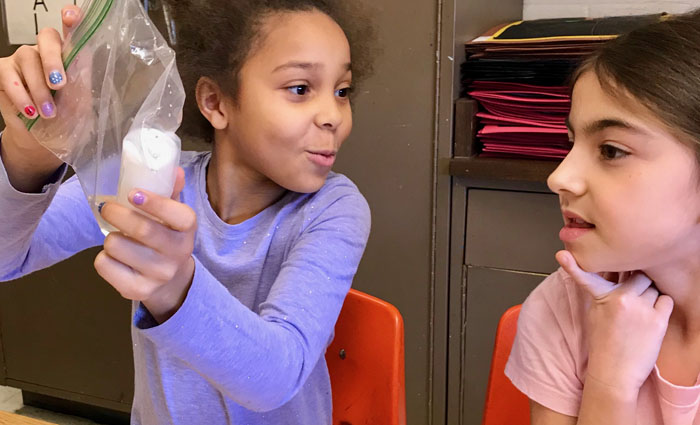 two girls work on a science experiment together