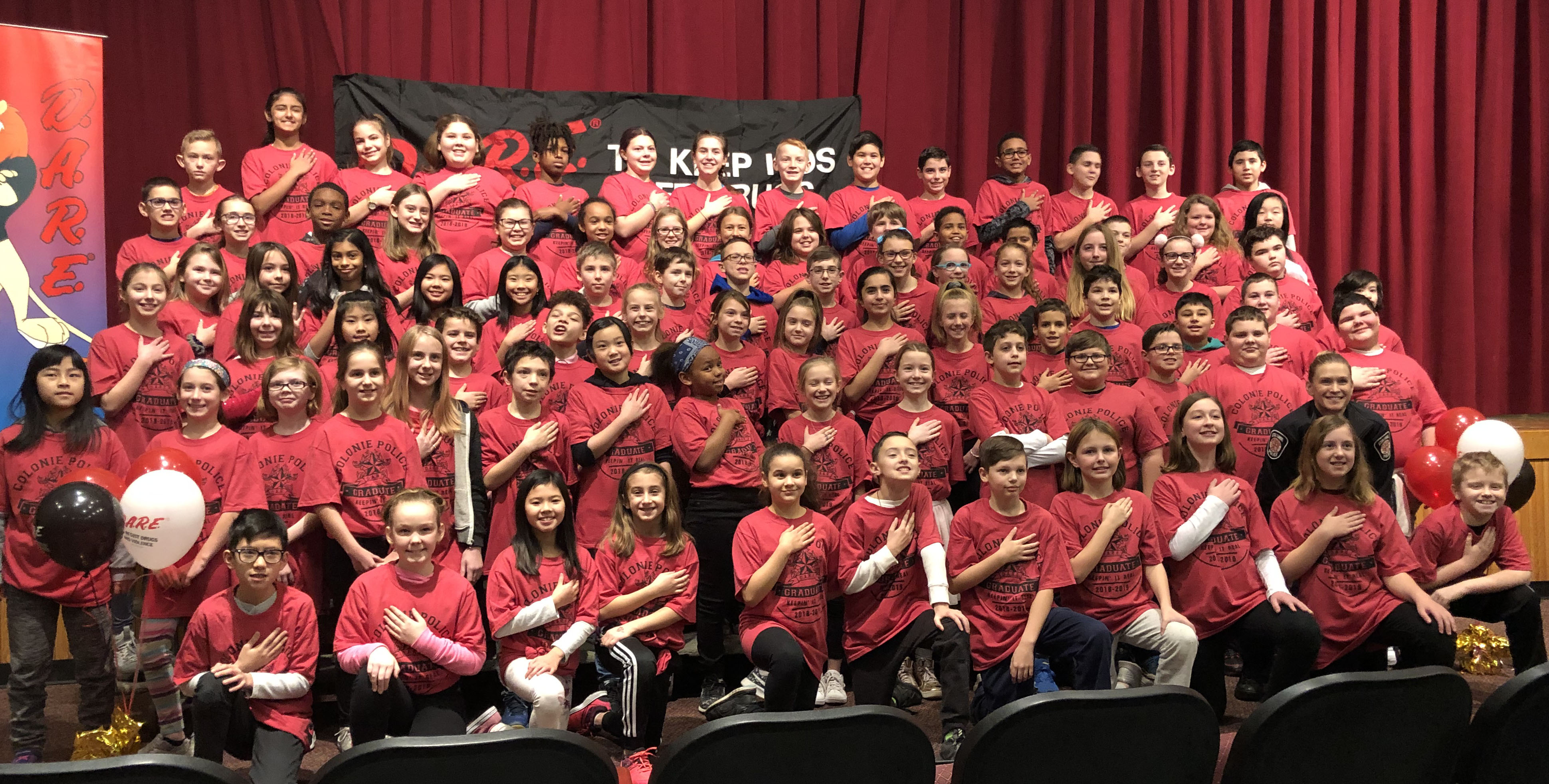 large group of students pose in their red shirts with DARE certificates