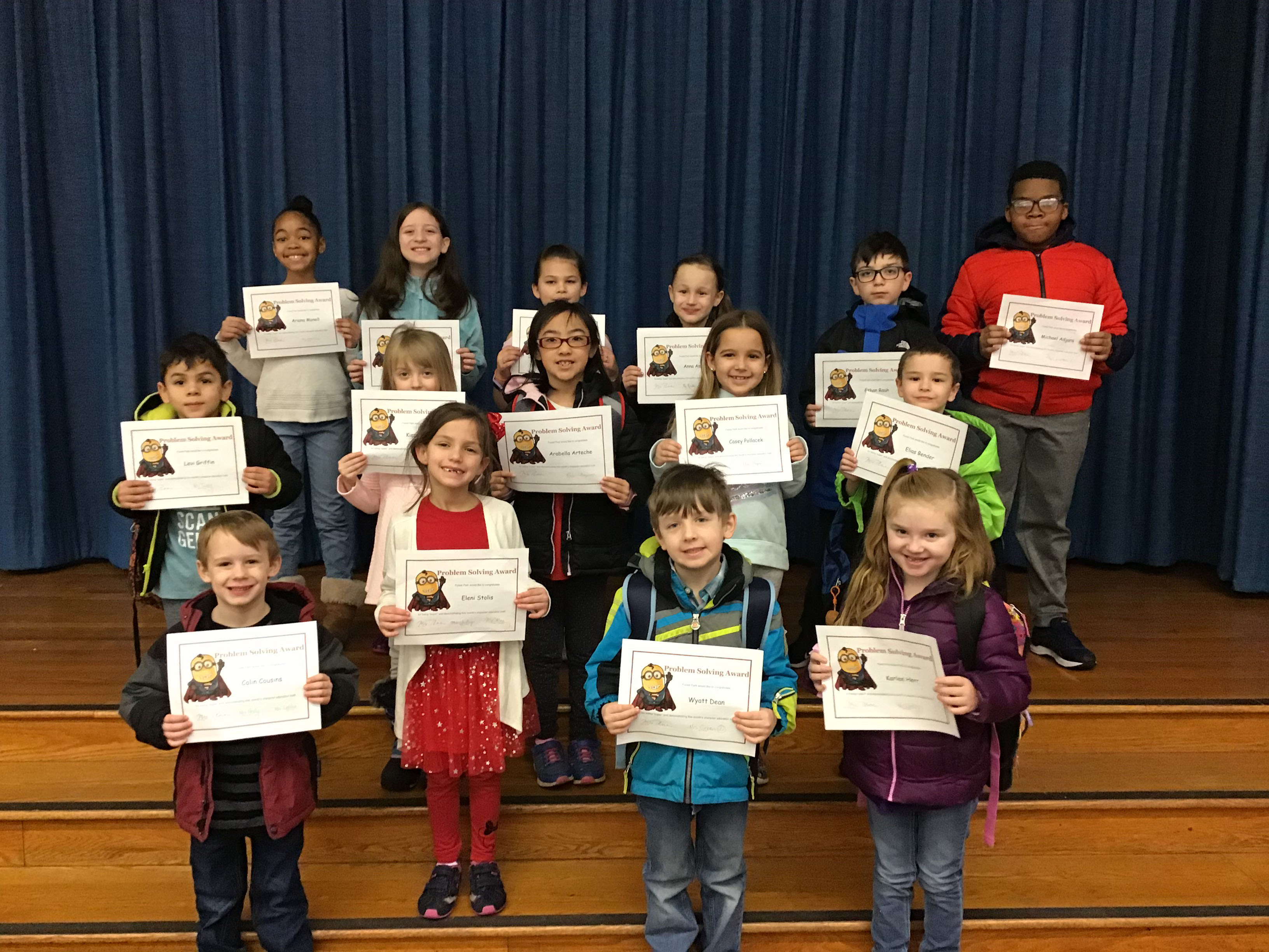 group of children stand with their award certificates
