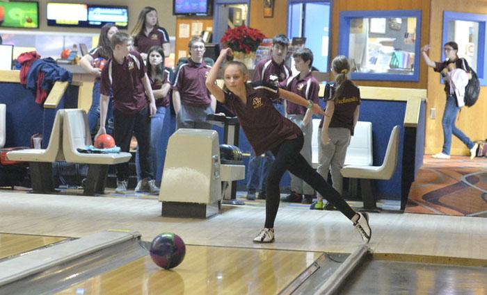 girl rolls a bowling ball down the lane