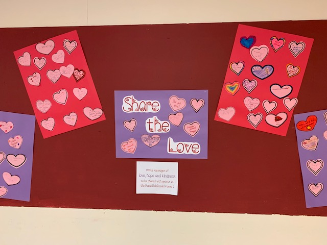 bulletin board covered with paper hearts and message of hope