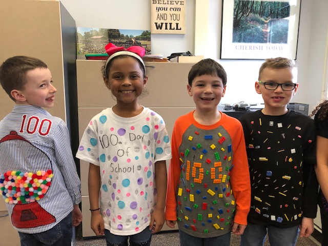 4 students show off their 100 day shirts
