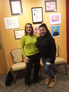 student stands with teacher in front of student artwork