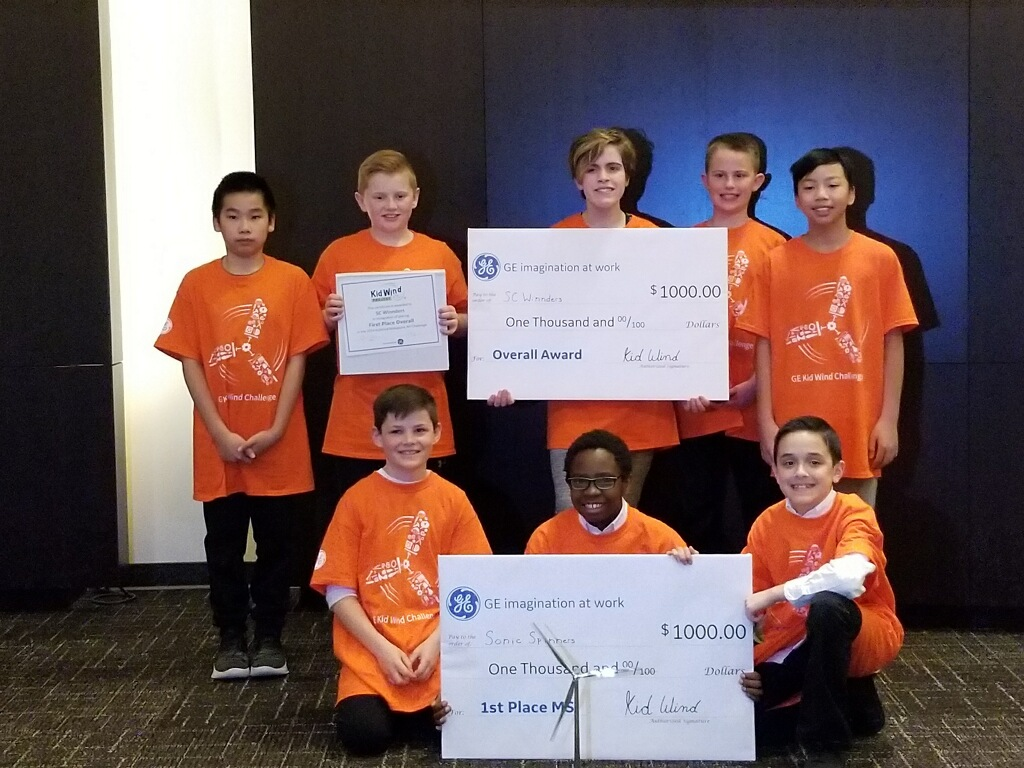 group of students show off their big checks